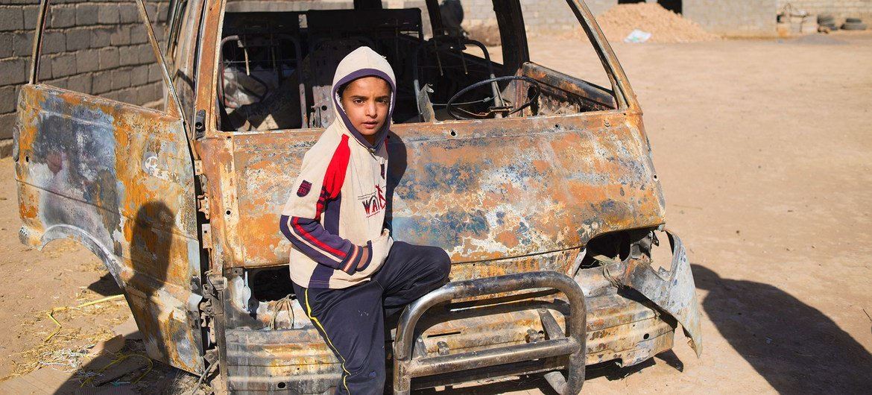 من الأرشيف: صبي صغير في العراق يقف بجانب سيارة أحرقها داعش.