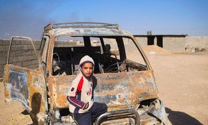 A young boy in Iraq stands next to a car that was torched by ISIL. (file)