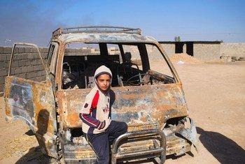 इराक़ में एक लड़का, कार के एक मलबे पर बैठा हुआ. इस कार को, आइसिल के लड़ाकों ने आग लगा दी थी. (फ़ाइल)