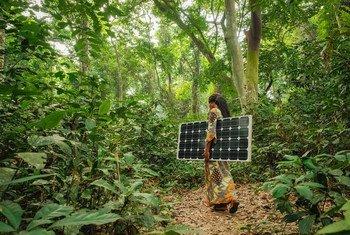 A Yangambi, dans le nord de la République démocratique du Congo, une femme transporte un panneau solaire
