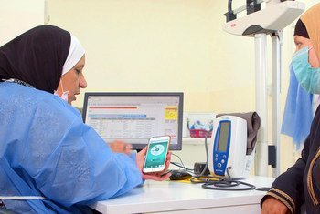 जॉर्डन में एक नर्स, एक फ़लस्तीनी शरणार्थी को स्मार्टफ़ोन पर ऐप दिखा रही है.