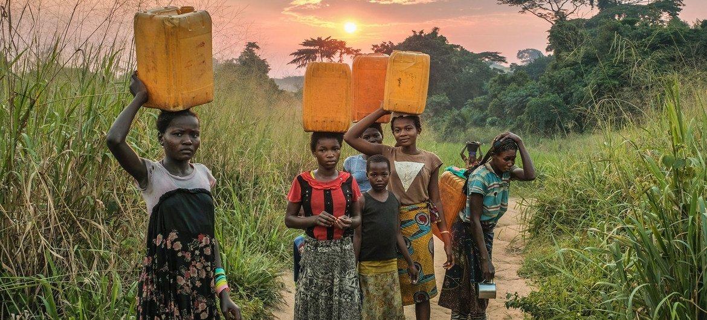 Jóvenes tienen que caminar mucho para recoger agua en Yangambi, República Democrática del Congo.