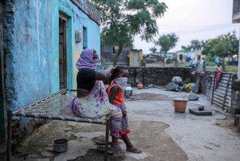 سيّدة تمشط شعر حفيدتها خارج منزلهما في الهند.
