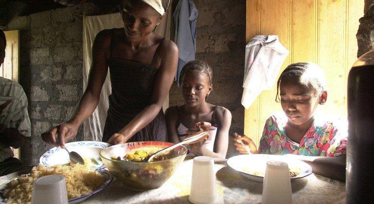 Una familia comiendo. La casa no tiene electricidad y los alimentos se cocinan fuera de la vivienda.