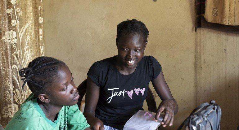 Angures Buba (kulia) na mwenzake wakisikiliza matangazo ya shule kwa njia ya redio huko Sudan Kusini.