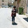 طفل يبلغ من العمر 8 سنوات يسير على طول الشارع في المدينة القديمة في الخليل باتجاه الحاجز العسكري الذي يجب أن يمر به للوصول إلى مدرسته.