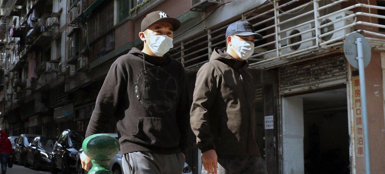 澳门街头,市民戴着口罩。截至3月17日,澳门累计报告12例确诊病例。10例本土感染病例均已康复出院。另外两例为境外输入病例,分别来自葡萄牙和西班牙。