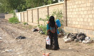 A woman, carrying her child who suffers from severe malnutrition and health complications, walks to a health centre in Hudaydah governorate, Yemen.