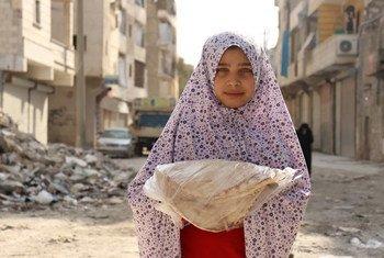 فتاة في حي الصالحين الفقير في حلب تحمل الخبز الذي يقوم بتوزيعه برنامج الأغذية العالمي