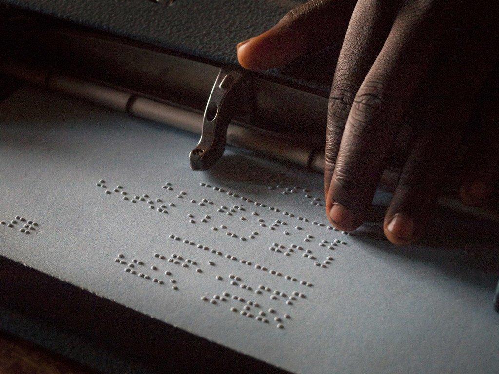 Un enfant lisant en braille dans un lycée en Ouganda.