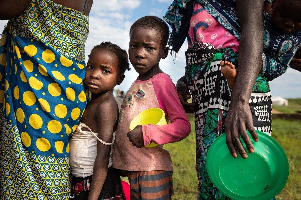 在莫桑比克贝拉的一个疏散中心,受飓风埃洛伊斯影响的家庭正在排队领取食物。