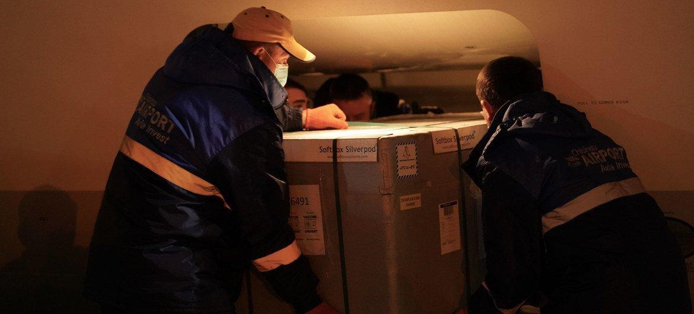 Trabalhadores de aeroporto de Moldávia recebendo doses de vacina da Covax
