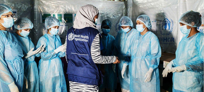 أخصائية الوقاية من العدوى ومكافحتها في منظمة الصحة العالمية تقدم مشورة للممرضات في منشأة صحية في مخيم كوتوبالونغ في بنغلاديش بشأن كيفية الوقاية من الإصابة بالفيروس أثناء علاج المرضى.