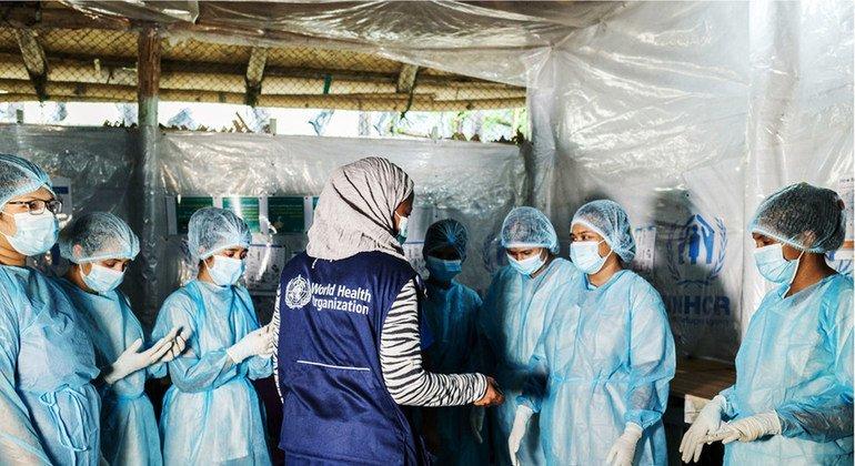 أحد المتخصصين بالوقاية من العدوى ومكافحتها في منظمة الصحة العالمية يقدم مشورة للممرضات في منشأة صحية في مخيم كوتوبالونغ في بنغلاديش وكيفية حماية أنفسهم من الإصابة بالفيروس.