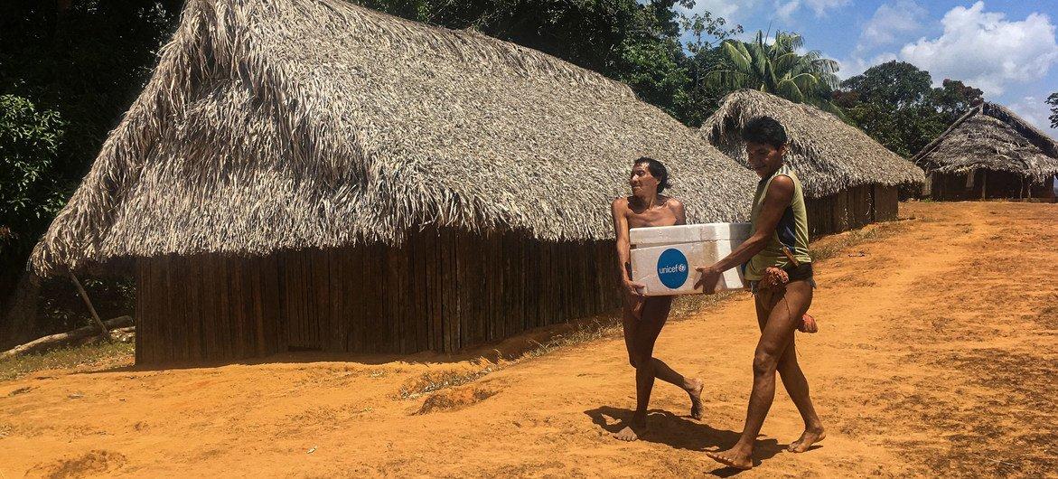 Dois homens da etnia Eñepa transportam vacinas para o ambulatório rural de San José de Kayamá, na Venezuela, em fevereiro de 2020.