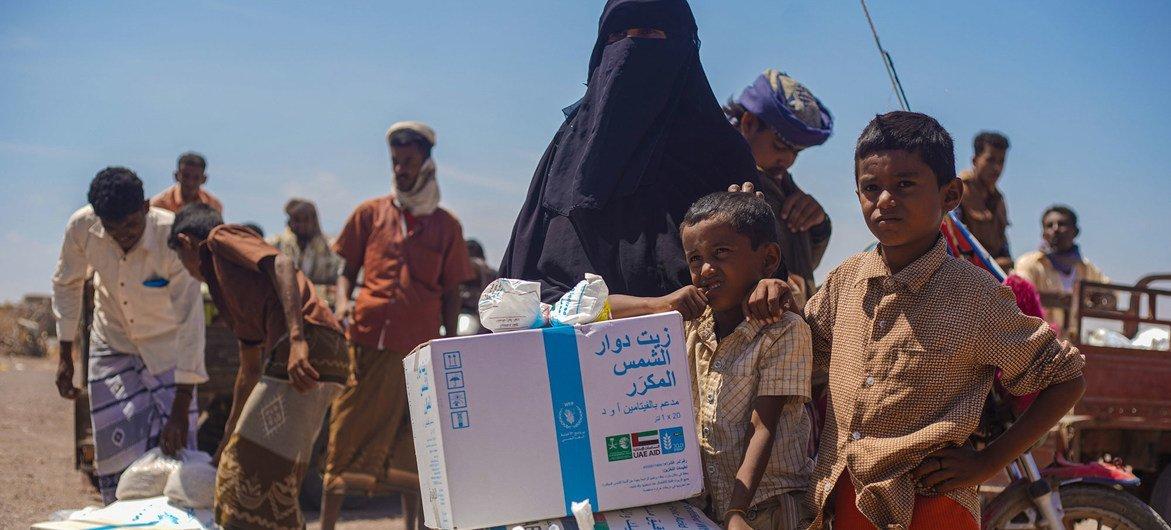 Une famille reçoit une aide alimentaire à un point de distribution de vivres à Ras al'Arah, dans le gouvernorat de Lahj, au Yémen.
