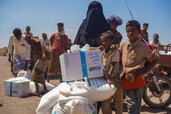 Familia ikipokea msaada wa chaakula katika kituo cha kusambaza chakula huko Ras al'Arah huko Lahj Governorate nchini Yamen