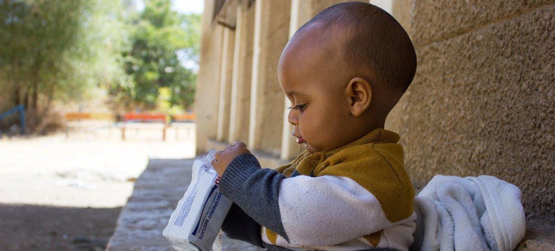 Un garçon de 7 mois dans l'ouest du Tigré mange un biscuit à haute teneur énergétique pour améliorer son niveau de nutrition.