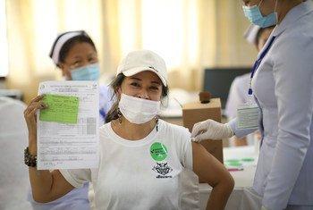 امرأة تُظهر بطاقة التطعيم الخاصة بلقاح كوفيد -19 في جمهورية لاو الديمقراطية الشعبية.