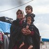 A widow holds her grandson in a displaced persons camp in northern Idlib Governorate, Syria.