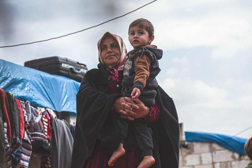 Une veuve tient dans ses bras son petit-fils dans un camp de déplacés dans la région d'Idlib, en Syrie.