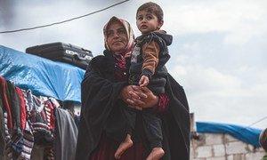 叙利亚伊德利卜北部的一处流离失所者营地内,一位失去了丈夫的女性抱着自己的孩子。