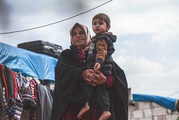 सीरिया के उत्तरी इदलिब गवर्नरेट के एक शिविर में एक विधवा महिला अपने पोते के साथ.