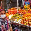 A woman works as a fruit vendor in Dhaka, Bangladesh. A single parent, she is accompanied at work by her two daughters.