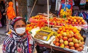 孟加拉国首都达卡的一位妇女正在集市上摆摊售卖水果。