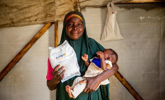 A parent  and girl  person   nutrient  from the World Food Programme astatine  a campy  for displaced radical   successful  Maiduguri, Nigeria.