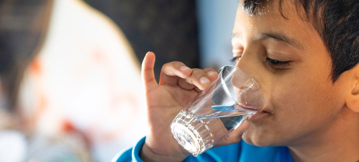A young boy drinks a glass of water from a new water network connected to the Za'atari Refugee Camp in Jordan.