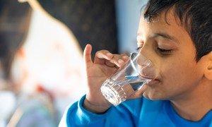Un jeune garçon boit un verre d'eau provenant d'un nouveau réseau d'eau relié au camp de réfugiés de Za'atari en Jordanie.