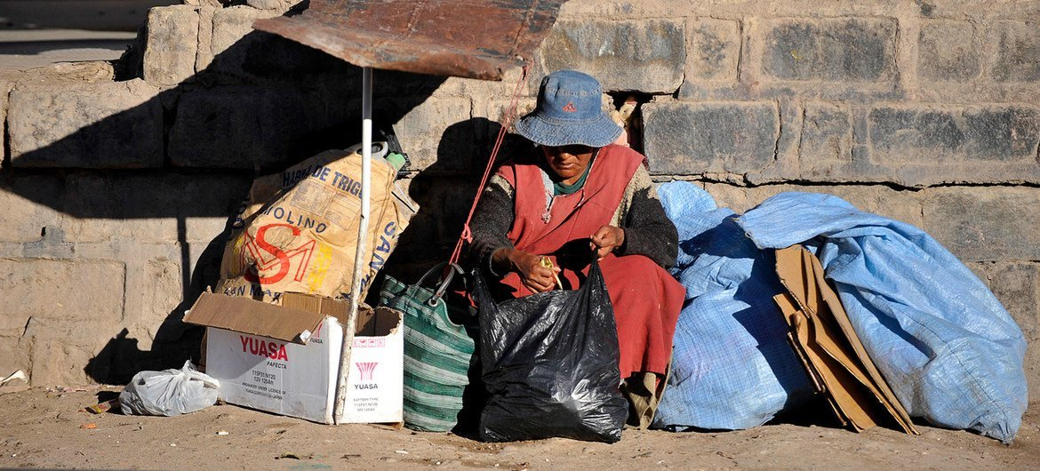 A stateless  pistillate   sits by a railway way   successful  Potosí, Bolivia.