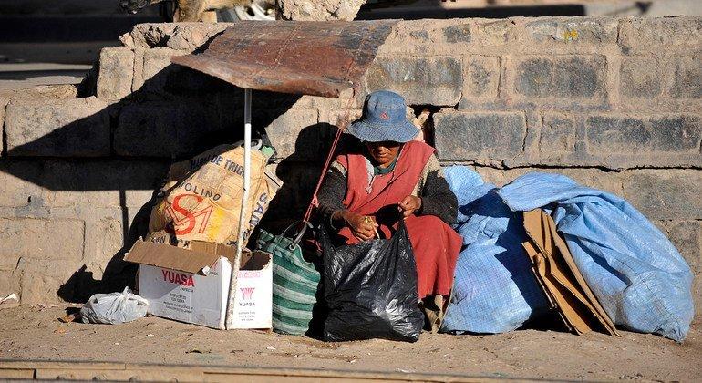 Una mujer sin hogar sentada junto a una vía férrea en la ciudad de Potosí, en Bolivia.