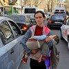 मोलदोवा के चिज़िनाउ में एक महिला अपने बच्चे को गोद में लिये हुए भीख माँग रही है.
