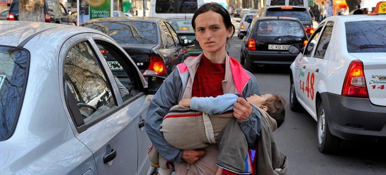 Женщина с ребенком попрошайничает на улицах Кишинева в Молдове.
