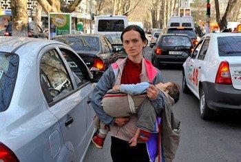 Uma mulher carrega sua criança enquanto pede dinheiro nas ruas da Moldávia