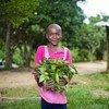 طفلة تحمل في يدها خضروات جنتها من حديقة منزلها في قرية في الكاميرون.