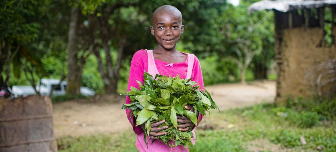 A child holds vegetables grown in her garden in a village in Cameroon.