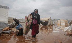 سيّدة تحاول إنقاذ حاجياتها بعد أن أغرقت الفيضانات مخيمها الواقع في شمال غرب سوريا في كانون الثاني/يناير 2021.