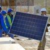 Men install solar panels for a hospital in Yemen.