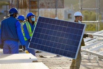 Des hommes installent des panneaux solaires pour un hôpital au Yémen.
