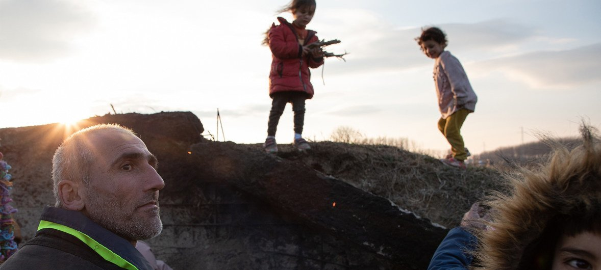 A Syrian family prepares to huddle down by a fire out of the wind while children gather branches to burn, as they deliberate how to get home after a failed crossing attempt at the Edirne border with Greece.