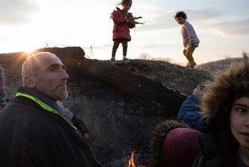 Erdine, nord-ouest de la Syrie. Une famille syrienne se protège du vent à la tombée de la nuit. Les enfants ramassent des branches pour faire un feu de camp tandis que les adultes réfléchissent à leurs options après avoir échoué à entrer en Grèce.