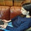 लैपटॉप पर काम कर रही एक युवती सुनने के लिये इयरबड्स का इस्तेमाल कर रही है.