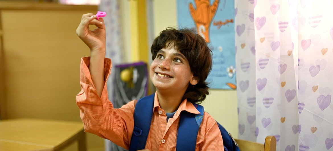 Mahmoud, who has autism, is holding the letter he was asked to find at the resource room in Egypt.