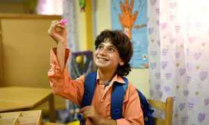 No Egito, Mahmoud, que tem autismo, participa de uma atividade com letras.