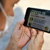 A person reads about COVID-19 on their cell phone. During the pandemic, smart phones with Internet have become a life-line for many, keeping them connected with their families and providing them with vital information.