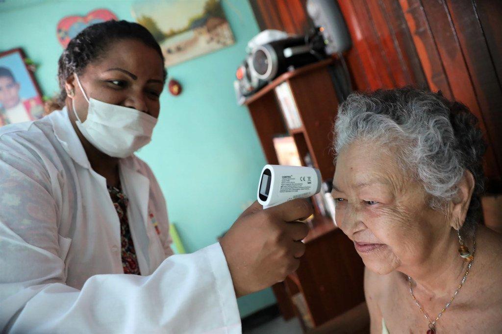 在委内瑞拉加拉加斯的一个社区,医生和护士正在挨家挨户开展运动,提高如何应对2019冠状病毒病。