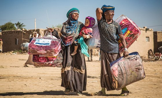A displaced family in Marib, Yemen, carries a winter aid package back to their shelter.
